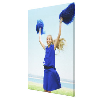 low angle view of a cheerleader holding up canvas print
