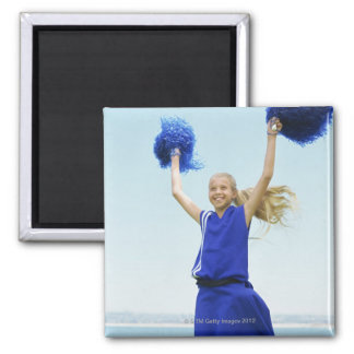 low angle view of a cheerleader holding up square magnet