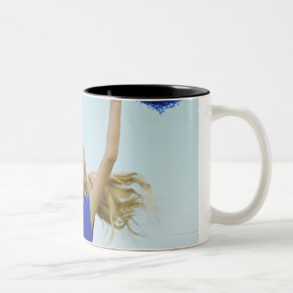 low angle view of a cheerleader holding up Two-Tone coffee mug