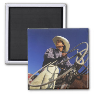 Low angle view of a cowboy riding a horse, square magnet