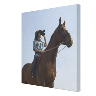 Low angle view of a teenage girl riding a horse canvas print