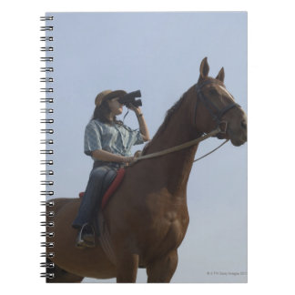 Low angle view of a teenage girl riding a horse notebook