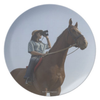 Low angle view of a teenage girl riding a horse plate