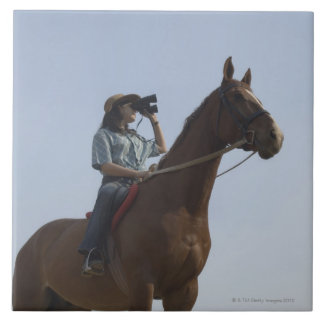 Low angle view of a teenage girl riding a horse tile
