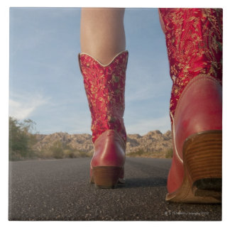 Low-angle view of woman wearing cowboy boots large square tile