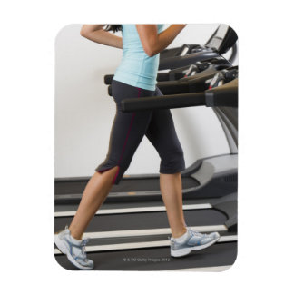 Low section of woman walking on treadmill magnets