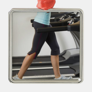 Low section of woman walking on treadmill Silver-Colored square decoration