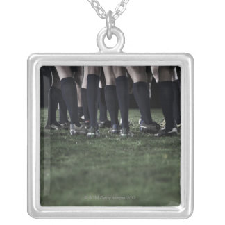 Lower section of a group of rugby players square pendant necklace
