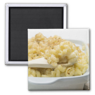 Macaroni cheese in baking dish with wooden square magnet