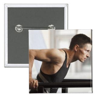 Male athlete using gymnastics equipment in gym 15 cm square badge