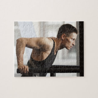 Male athlete using gymnastics equipment in gym jigsaw puzzle