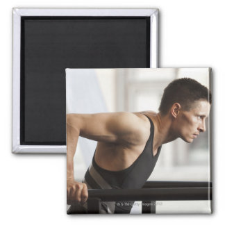 Male athlete using gymnastics equipment in gym square magnet
