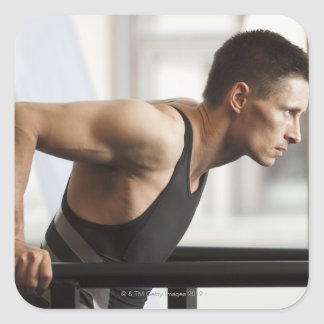 Male athlete using gymnastics equipment in gym square sticker