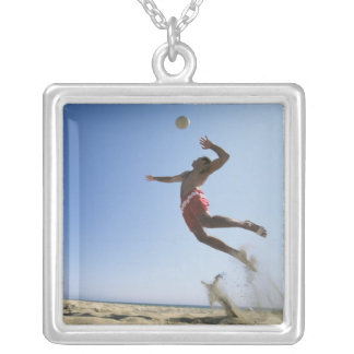 Male beach volleyball player jumping up to spike silver plated necklace