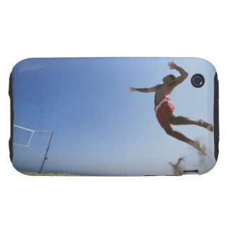Male beach volleyball player jumping up to spike tough iPhone 3 cases