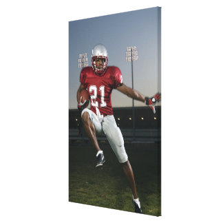 Male football player carrying football canvas print