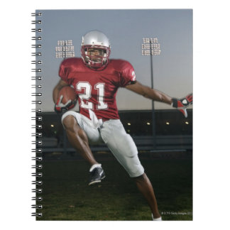 Male football player carrying football notebook
