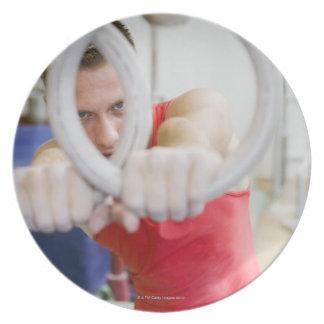 Male gymnast on rings dinner plate