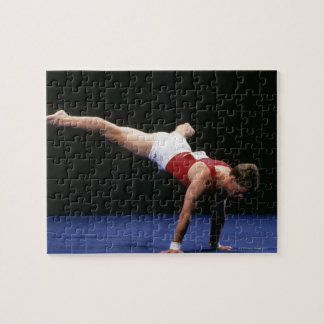 Male gymnast peforming a routine in the floor puzzle