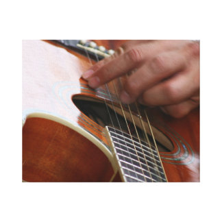male hand holding pick on acoustic guitar canvas prints