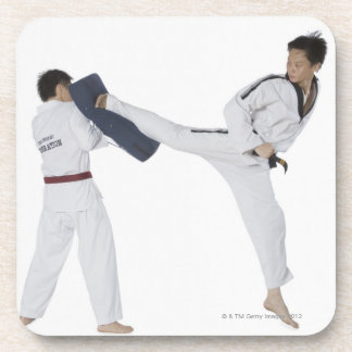 Male karate instructor teaching martial arts to 2 coaster