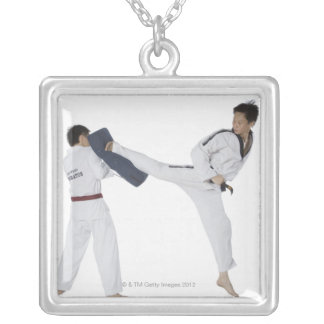 Male karate instructor teaching martial arts to 2 silver plated necklace