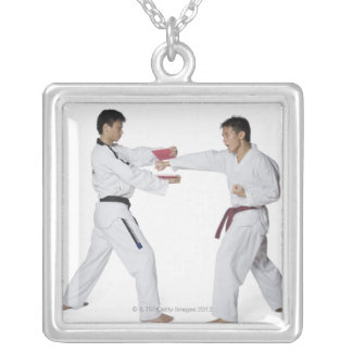 Male karate instructor teaching martial arts to silver plated necklace