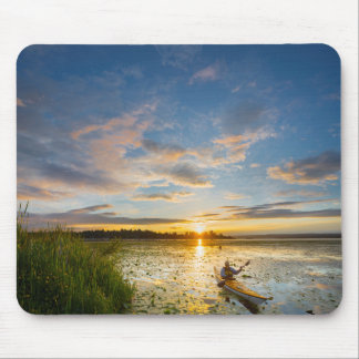 Male kayaker paddling sea kayak on still water mouse pad