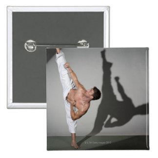 Male martial artist performing kick, studio shot 15 cm square badge