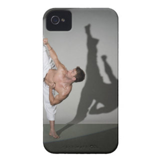 Male martial artist performing kick, studio shot iPhone 4 covers