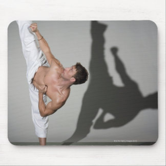Male martial artist performing kick, studio shot mouse mat
