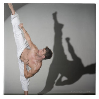 Male martial artist performing kick, studio shot tile