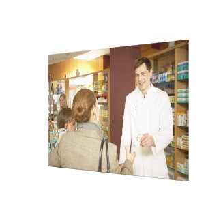 Male pharmacist handing medicine over to young canvas print