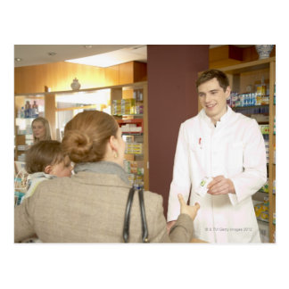 Male pharmacist handing medicine over to young postcard