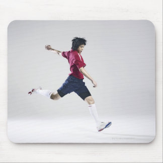 Male soccer player preparing to kick ball mouse pad