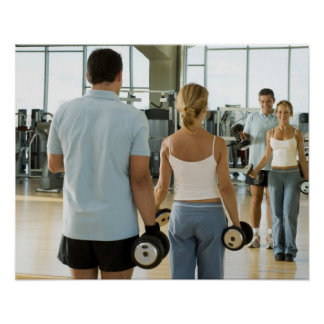 Man and woman lifting hand weights in front of a poster