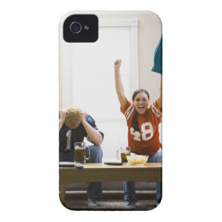 Man and woman sitting on sofa watching football iPhone 4 covers