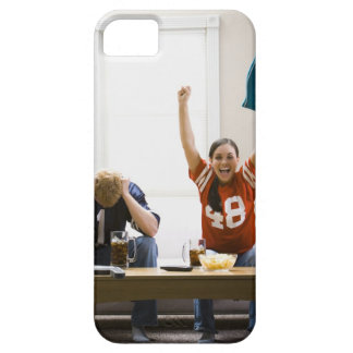 Man and woman sitting on sofa watching football iPhone 5 covers
