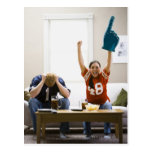 Man and woman sitting on sofa watching football post cards