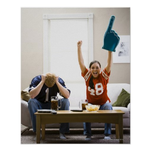Man and woman sitting on sofa watching football posters