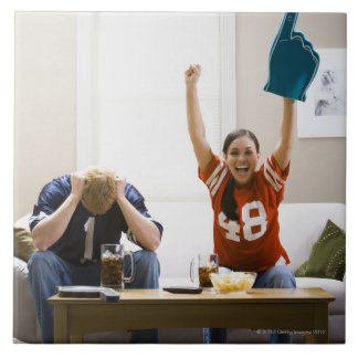 Man and woman sitting on sofa watching football tile