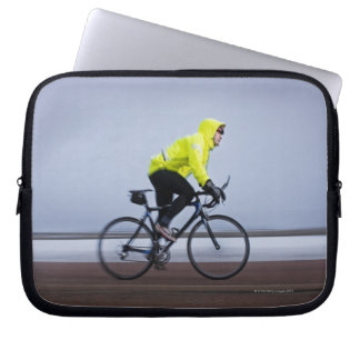 Man bicycles on a cold and foggy winter day. laptop sleeve