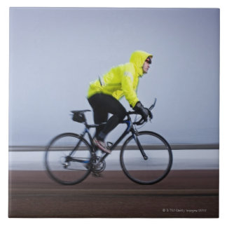 Man bicycles on a cold and foggy winter day. tile