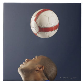 Man bouncing soccer ball on his head 2 tile