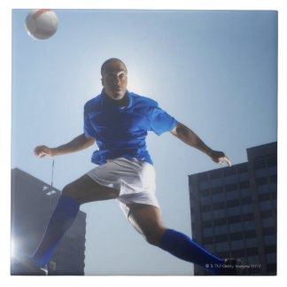 Man bouncing soccer ball on his head large square tile