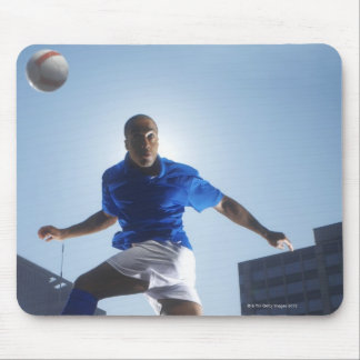 Man bouncing soccer ball on his head mouse mat