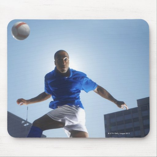 Man bouncing soccer ball on his head mousepad