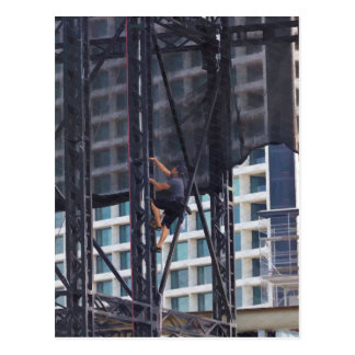 Man climbing up a steel ladder post card