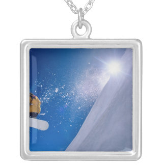 Man flying through the air on a snowboard with silver plated necklace