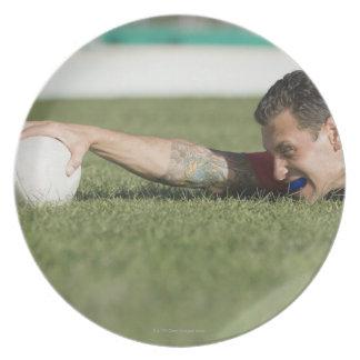 Man grabbing rugby ball dinner plate